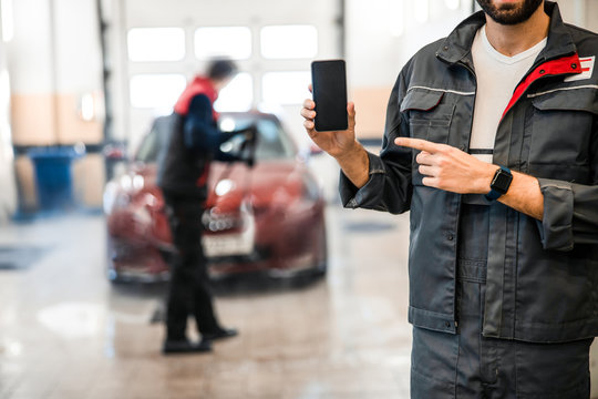 Caucasian mechanic pointing at his cellular phone