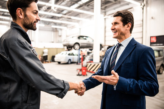 Smiling mechanic and his customer shaking hands