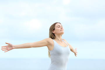 Happy woman breathing fresh air outstretching arms on the beach - fototapety na wymiar