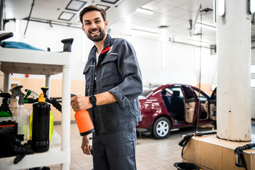 Handsome car washer choosing a pump sprayer