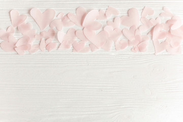 Cute pink pastel hearts on white wooden background with space for text. Flat lay. Happy valentines day. Pink paper heart cutouts on white,  gentle image,  greeting card.