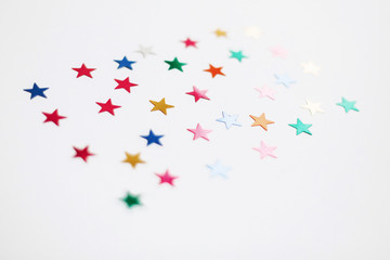 Colorful stars confetti or glitter on white background. Party backdrop. Stylish atmospheric image. Happy birthday concept. Holiday decorations. Magic and Christmas.