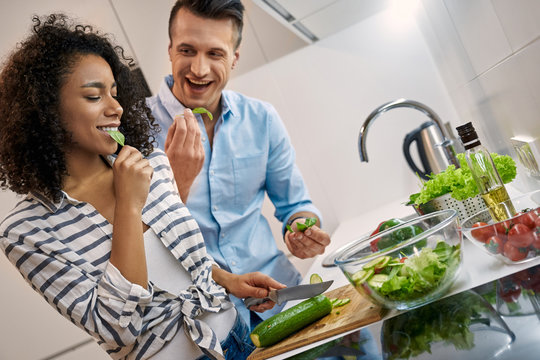 Young adult man and african american woman cooking healthy food together