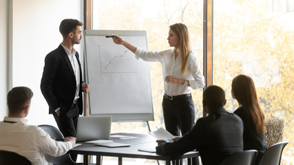Company boss and business trainer make presentation during group meeting