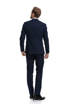 young businessman in navy blue suit looking up and dreaming