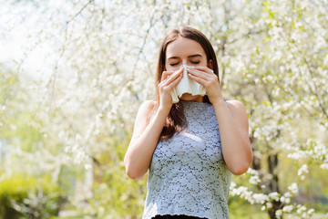 Sneezing young girl with handkerchief among blooming trees in spring park. Concept of allergy