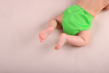 Baby's feet and green reusable diaper.  Zero waste baby care and massage concept.