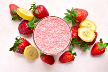 Delicious strawberry banana smoothie in a glass with ingredients for making. Top view with copy space.