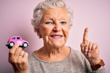 Senior beautiful woman holding small car standing over isolated pink background surprised with an...