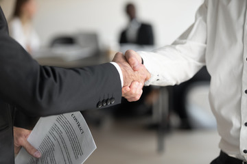 Closeup view boss holding contract paper shake hands with client