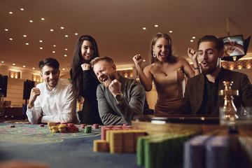 Friends gambling betting in a casino.