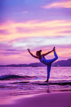 Woman practices yoga at seashore