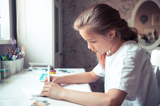 Beautiful pensive girl drawing sketch at her table with light from window