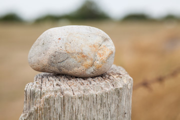 Stone resting on a wooden pole of a fence