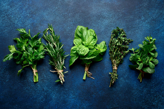 Bunchs of variety fresh aromatic herbs. Top view with copy space.