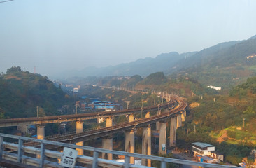 Fototapeta Traffic track in the middle of the mountains.  China railway rail transportation line.  Railway viaduct