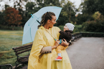 Beautiful and happy middle age woman with her baby walking in city park on rainy day.. Fotobehang