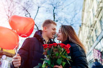 Valentines day date. Man and woman about to kiss outdoors. Couple walking with roses flowers and balloons