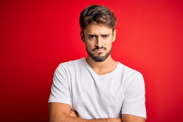 Young handsome man with beard wearing casual t-shirt standing over red background skeptic and...