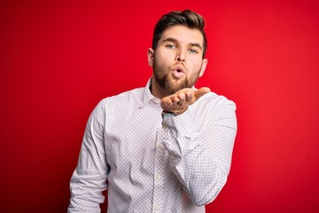 Young blond businessman with beard and blue eyes wearing elegant shirt over red background looking at the camera blowing a kiss with hand on air being lovely and sexy. Love expression.