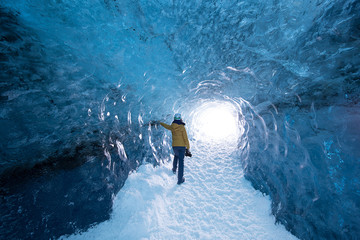 Spectacular natural landscapes inside a blue ice cave, with a woman in yellow looking outside the cave in Iceland