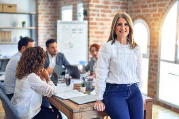 Group of business workers working together. Middle age beautiful businesswoman standing smiling...