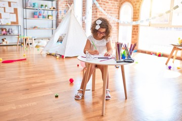 Beautiful toddler wearing glasses sitting drawing using paper and pencils at kindergarten