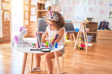 Beautiful toddler wearing glasses and princess crown sitting drawing using paper and marker pen at...