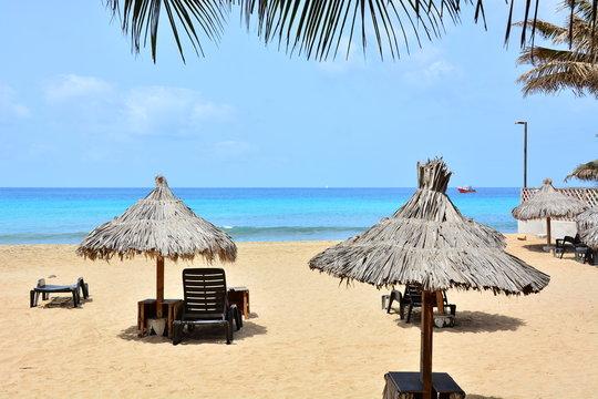 Sun umbrellas, beach umbrellas on a sandy beach and a blue, turquoise ocean, sea on Sal Island in Cape Verde, Cabo Verde