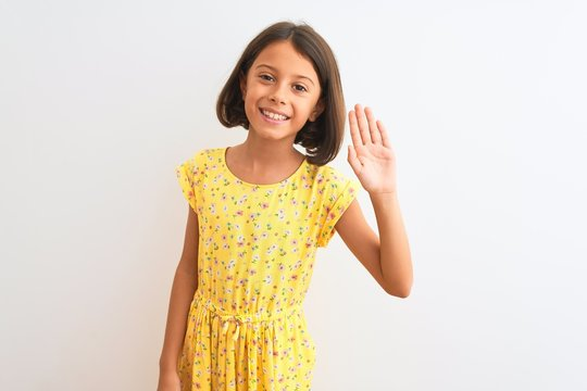 Young beautiful child girl wearing yellow floral dress standing over isolated white background Waiving saying hello happy and smiling, friendly welcome gesture