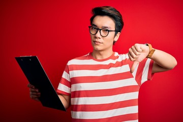 Young handsome chinese inspector man wearing glasses holding clipboard checklist with angry face, negative sign showing dislike with thumbs down, rejection concept