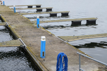Empty jetties with blue electric boxes and hose, a yacht marina out of season waiting in the cold sea water for spring