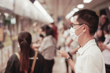 Middle aged Asian man wearing glasses and medical face mask waiting for public train with crowd,  Wuhan coronavirus, covid-19 virus outbreak, air pollution and health concept