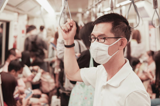 Middle aged Asian man wearing glasses and medical face mask on public train,  coronavirus,  covid-19 virus post pandemic, air pollution and health, new normal, reopening concept