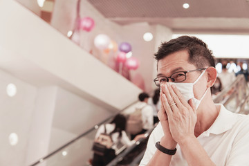 Middle aged Asian man wearing glasses and medical face mask, sneezing and coughing, Wuhan...