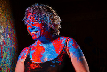 portrait of a happily smiling lady with colorful red and blue bodypainting against dark background