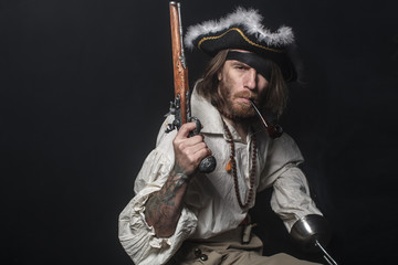 medieval bearded pirate with a sword and gun. concept photo of handsome man in a pirate vintage costume with pistol and saber