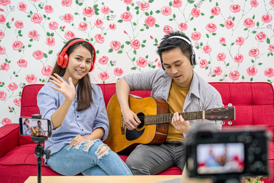 Asian Vlogger of married couple playing and sharing the music to attendee via mobile phone by social media channel, camera taking video and stream live, vlog and influencer freelance concept