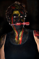 attractive European (Caucasian) woman with mainly black bodypainting with red and golden colour accents - she is carrying a round red brush with her teeth and looks to the right side
