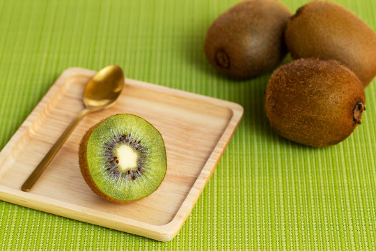 Open kiwi fruit in a wooden square plate over a green table mat background.