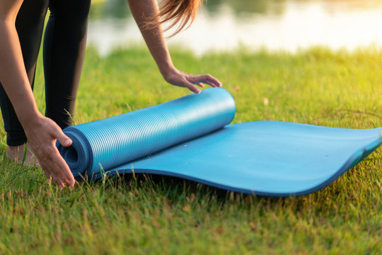Young asian woman rolling blue yoga mat or fitness mat prepare to exercise in park, Healthy concept, Mind-body improvements concept.