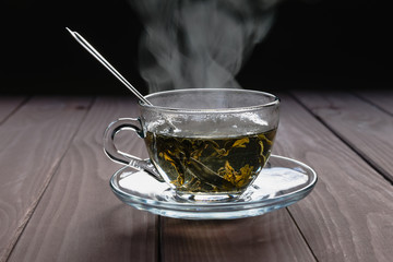 Photo sur Aluminium The A transparent cup of hot green tea with large leaves and steam on a dark background