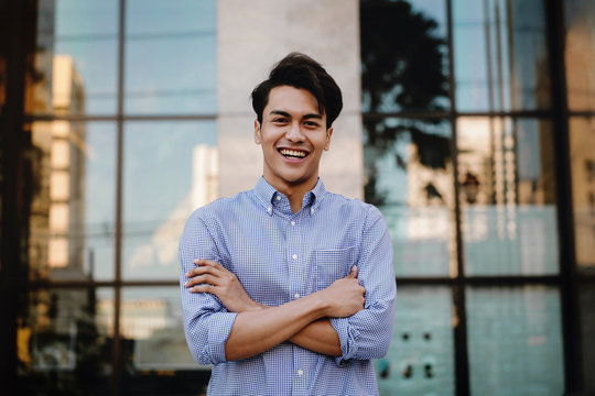 Happy Young Businessman Standing with a Big Smile in the City. Crossed Arms and Looking at Camera