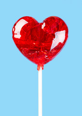 Shiny red lollipop in the shape of a heart for Valentine's day.