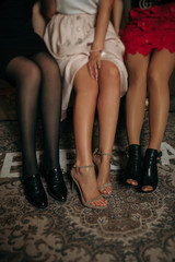 long naked sexy legs of three girls in open shoes with spikes