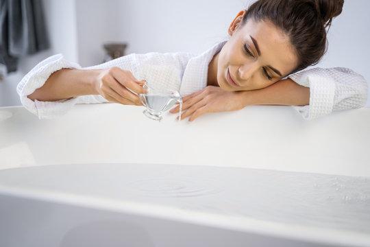 Girl adding the oil to a bathtub