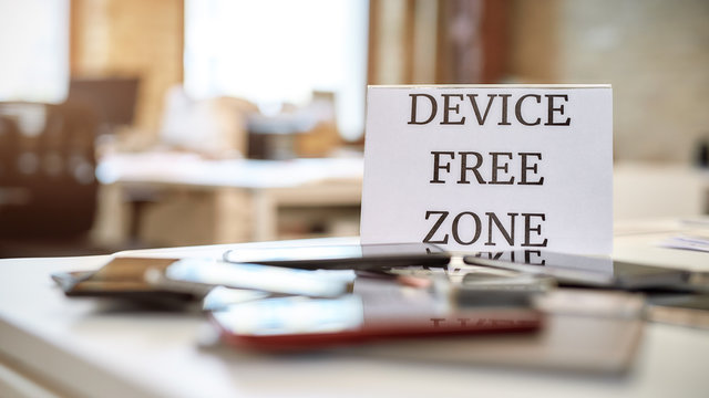 No tech allowed. Close up of mobile phones on the office table with device free zone sign