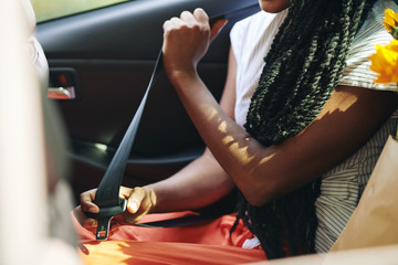 Cropped image of young woman fastening seat belt in taxi car