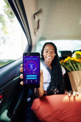 Positive young woman sitting on taxi backseat and showing smartphone with smart charger application