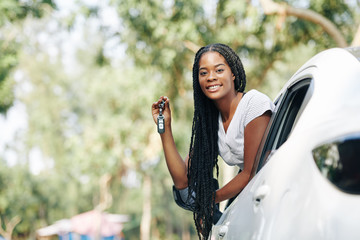 Happy young woman sticking out of car window and showing electronic car keys